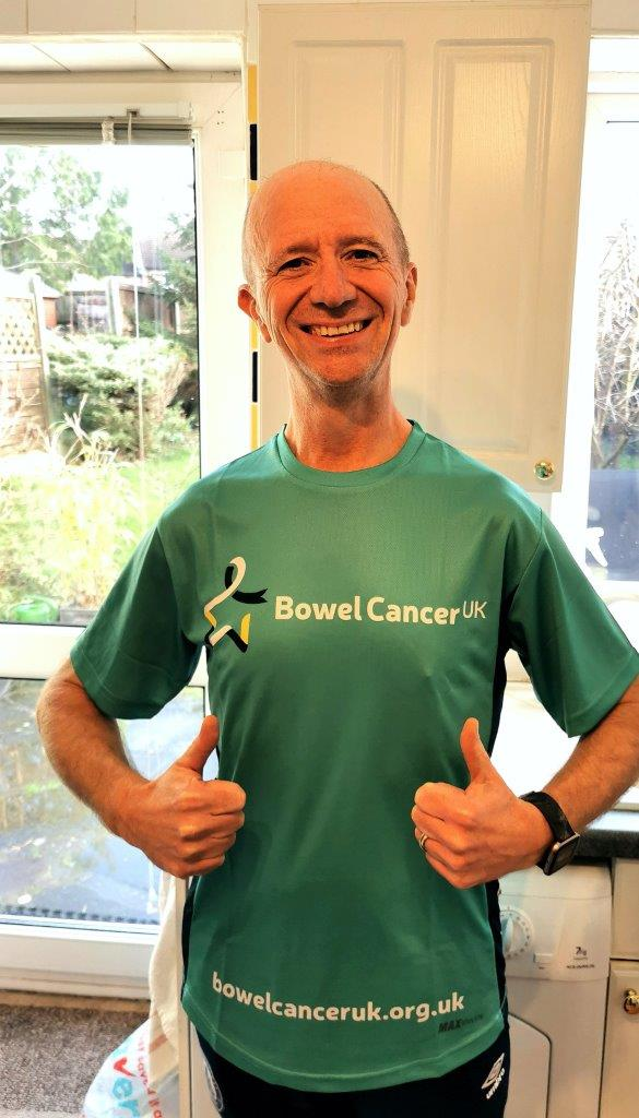 Andy Thomson diagnosed with stage 2 bowel cancer in 2020 wearing bowel cancer uk t shirt, smiling thumbs up