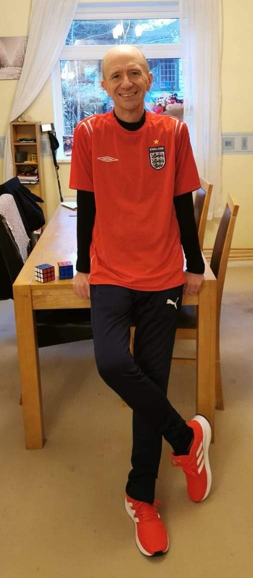 Andy Thomson smiling wearing his red Umbro England t shirt and red adidas trainers